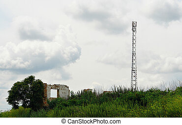 Telecommunication antenna tower among the ruins of brick...