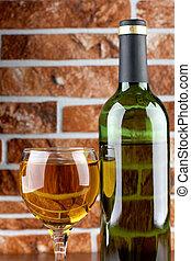 Wineglass on brick wall - Wine bottle and glass on brick...