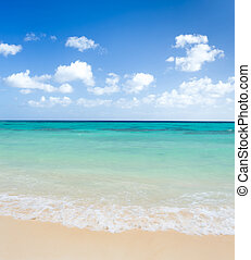 Sand beach with sea wave and blue sky background