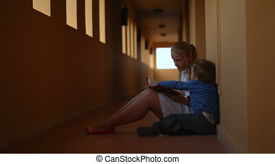 Mother and son with book in hotel hall