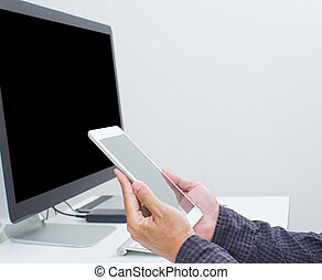 Man working on tablet with blank screen computer background