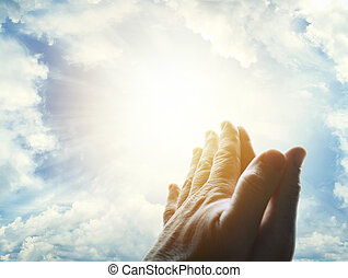 Prayer - Hands together praying in bright sky