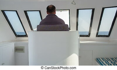 Driving a yacht - Back view of a man driving a yacht