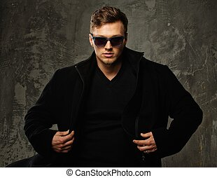 Stylish young man in black coat and sunglasses