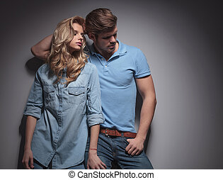 fashion couple in a sexy pose looking to their side against...