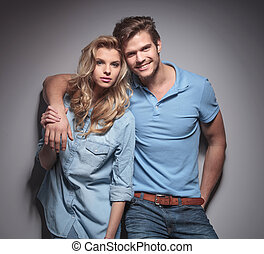 fashion couple in casual clothes standing embraced
