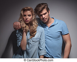 portrait of a young fashion couple standing embraced