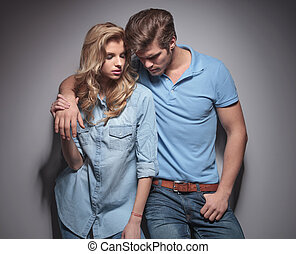 man looking down while holding his girlfriend