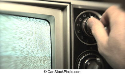 Static TV - Man 30s turning channel knob on retro television...