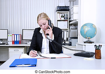 Office work - A businesswoman on the phone and taking notes...