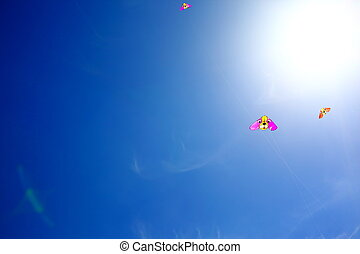 Sunny blue sky with flying kites