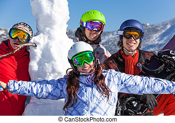 Snowboarders and snowman wearing goggles - Four happy...