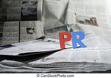 Word PR on newspaper. Wooden letters