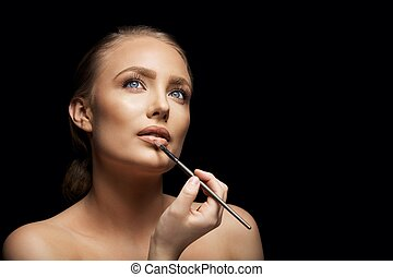 Attractive woman applying lip gloss - Close up image of...