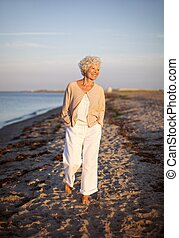 Senior woman walking on the beach - Image of senior woman...
