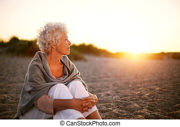 Old woman sitting on the beach looking away at copyspace...