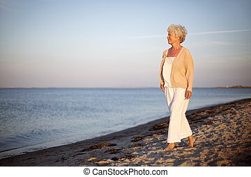 Relaxed old lady strolling on the beach