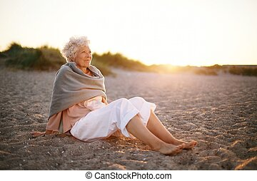 Relaxed elderly woman sitting on the beach - Image of...
