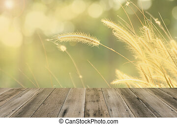 Wood floor with Foxtail weed grass flowers background