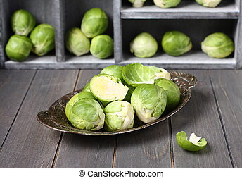 Fresh raw brussels sprouts in metal plate on  wooden background