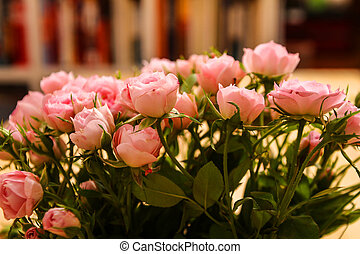 Roses - Bunch of small pink Roses in a glass vase over a...