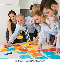 Business Colleagues Arranging Labels On Table - Business...