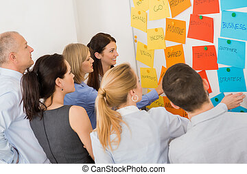 Colleagues Brainstorming In Front Of Whiteboard - Business...