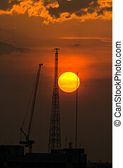 Industrial construction cranes and building silhouettes over sun at sunset.