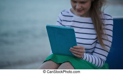 Young woman using tablet PC by the sea - Young woman sitting...