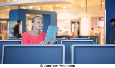Talking skype in the airport - Young woman sitting in the...