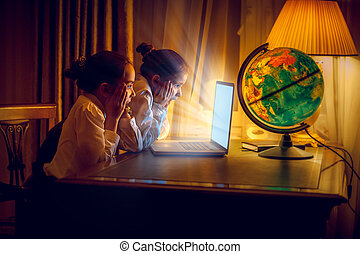 Girls looking with amazement at laptop at night