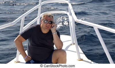 Phone talk on sailing yacht