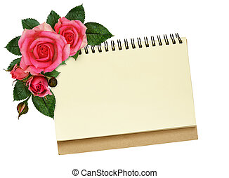 Notebook and rose flowers isolated on white