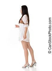 Side view of Asian woman with white short dress, full length...
