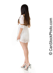 Rear view of Asian woman with white short dress, full length...