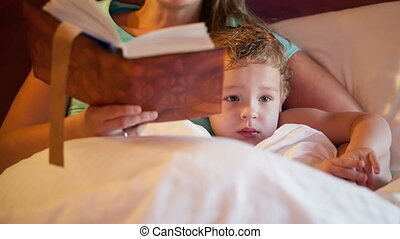 Bedtime reading - Tilt shot of mother and son during bedtime...