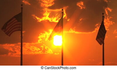American flags, sunset - Three American flags back lit by...