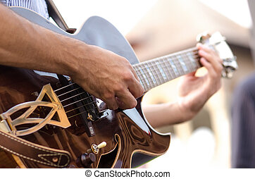 Man playing the guitar - Mans hands playing a guitar in a...