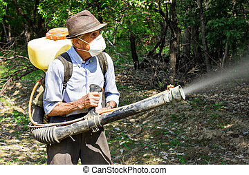 Peasant spraying the trees with chemicals in orchard