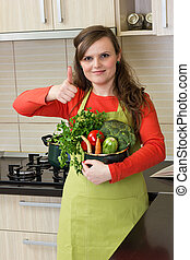 Beautiful happy young woman with apron holding a pot and making ok sign in her kitchen