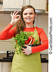Beautiful happy young woman with apron holdin a pot and making ok sign in her kitchen