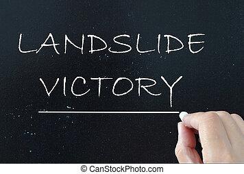 Landslide victory handwritten on a chalk board