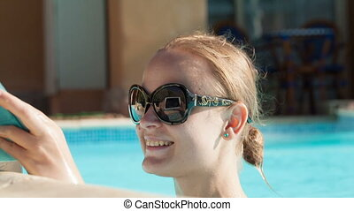 Young woman using a tablet poolside - Beautiful young woman...