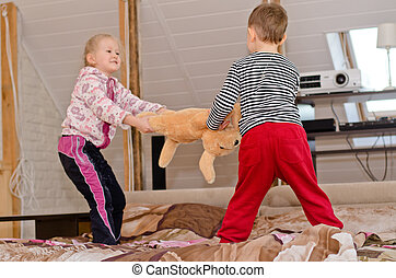 Cute brother and sister having a tug of war - Cute little...