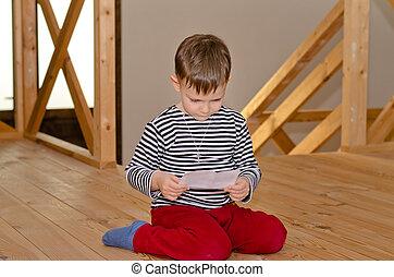 Chłopiec, Mały, czytanie, klęczący, podłoga