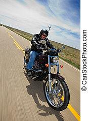 Biker ride - A biker taking a ride on a long strait rural...
