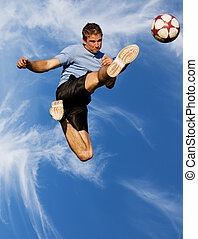 High kick - Athletic male high in the air kicking a soccer...