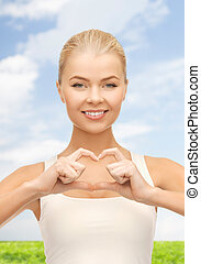 smiling woman showing heart shape gesture - love and gesture...