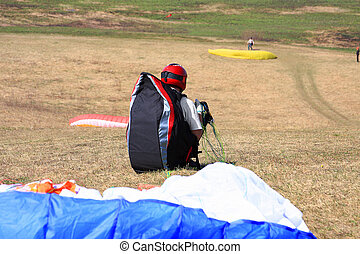 Paraglide - The glider pilot prepares for flight on a...