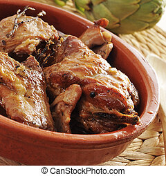 spanish roast rabbit - closeup of an earthenware bowl with...